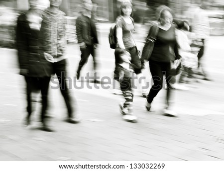 pedestrians walking in the streets in the modern city,black and white
