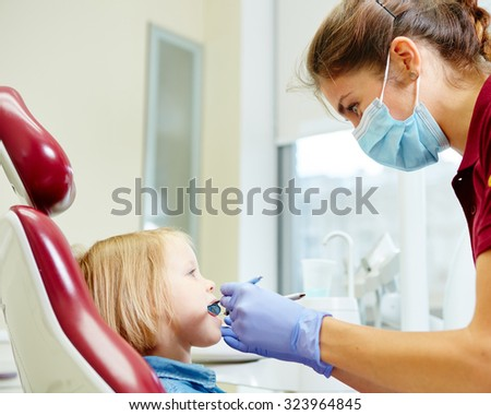 Pediatric dentist examining little girls teeth in the dentists chair at the dental clinic - stock photo