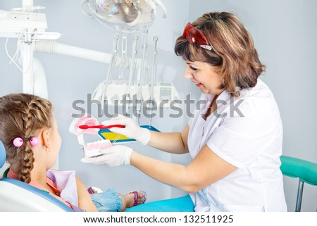 Pediatric dentist showing basic dental hygiene principles - stock photo