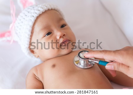 Pediatric doctor exams newborn baby girl with stethoscope in hospital. - stock photo