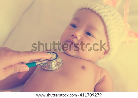 Pediatric doctor exams newborn baby girl with stethoscope in hospital. vintage style - stock photo