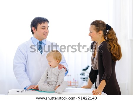 Pediatric doctor talking with mother while baby playing with stethoscope - stock photo