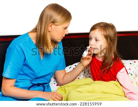 Pediatrician administrating nasal spray for the stuffy nose of her patient.  - stock photo