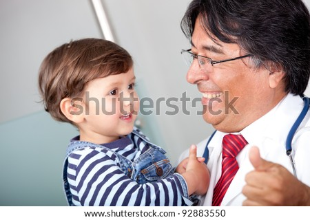 Pediatrician at the hospital holding a little boy - stock photo