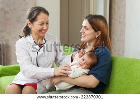pediatrician doctor examining newborn baby on mother's arms in house - stock photo