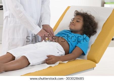 pediatrician doing abdominal examination - stock photo