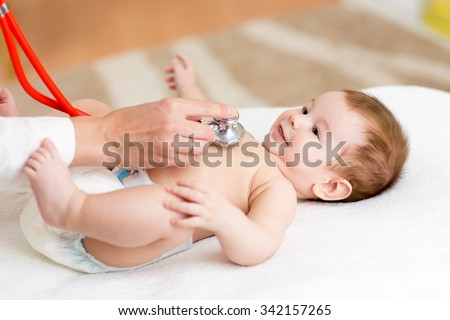 Pediatrician examines three months baby boy. Doctor using a stethoscope to listen to kid's chest checking heartbeat. Smiling child looking at doctor. - stock photo