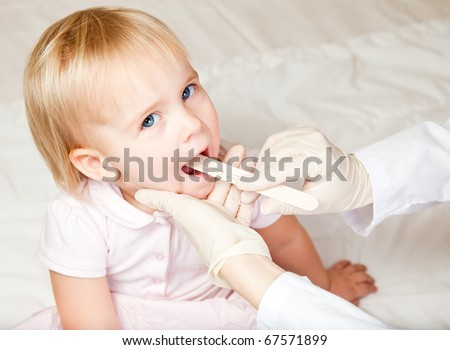 Pediatrician examining little girl's throat with tongue depressor