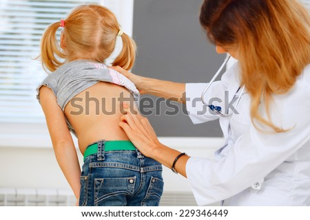 Pediatrician examining little girl with back problems. - stock photo