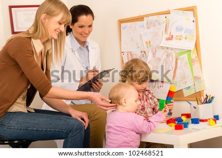 Pediatrician female observe children playing activity fill medical report