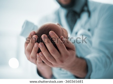 Pediatrician holding a beautiful newborn baby boy - stock photo