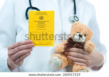 Pediatrician holding an international certificate of the vaccination - stock photo