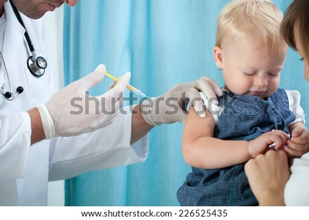 Pediatrician makes vaccination to small girl - stock photo