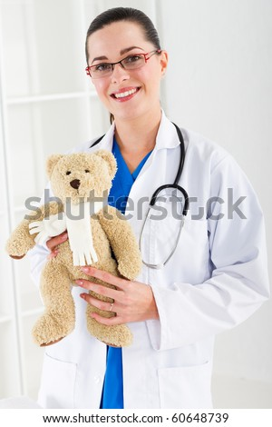 pediatrician with teddy bear - stock photo