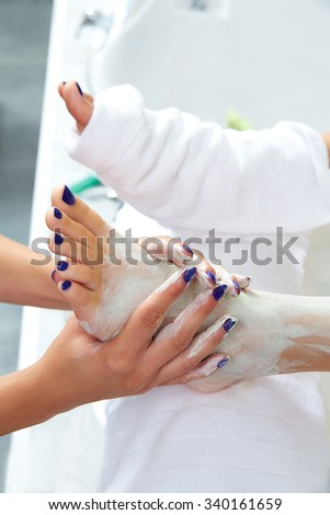 Pedicure applying nourishing moisturizer mask in legs of woman in nails salon - stock photo