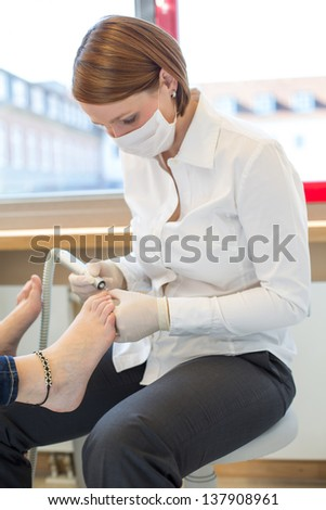 Pedicure at work in salon caring for customers foot nails - stock photo
