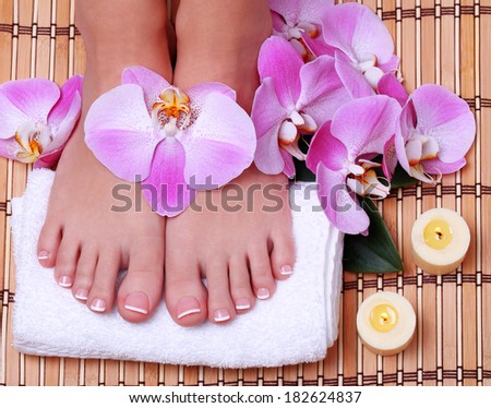 Pedicure. Beautiful female feet with french manicure and pink orchid flowers on bamboo mat.  Foot care. Spa Salon
