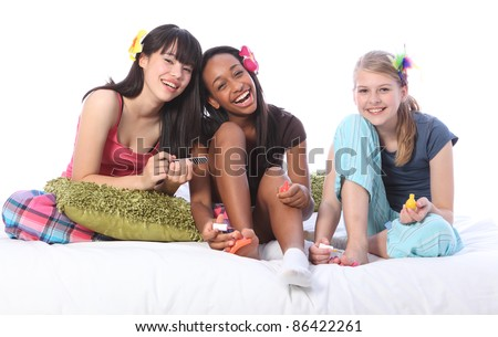 Pedicure fun at pyjama party for three teenage girl friends, a mixed race african american, oriental Japanese and blonde caucasian school mates all wearing flower or feather hair accessories. - stock photo
