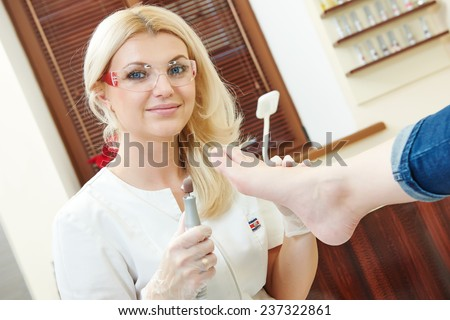 Pedicure nail technician worker perfoming procedure for foot care in beauty salon - stock photo