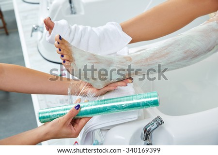 Pedicure nourishing moisturizer mask legs cling film wrap heat effect in nail salon - stock photo