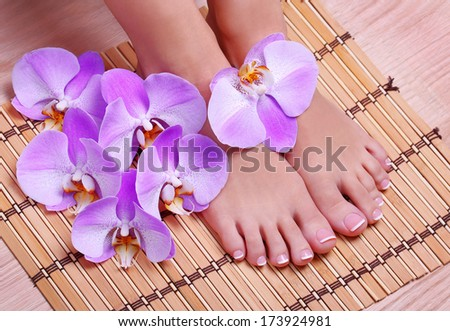 Pedicure with pink orchid flowers on bamboo mat. Beautiful female feet with french manicure. Foot care. Spa - stock photo
