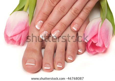 Pedicured feet and manicured hands with Easter tulips - stock photo