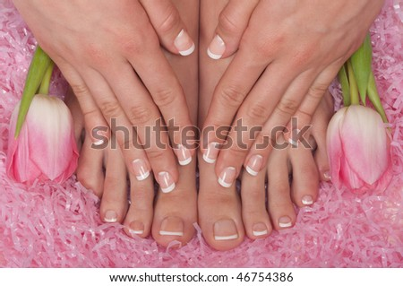 Pedicured feet, manicured hands and aromatic flowers in a spa - stock photo