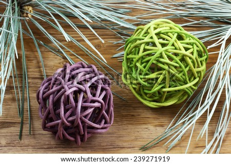Pedig decoration - purple and green tangled balls with whitegreen pine needles on wooden desk - stock photo