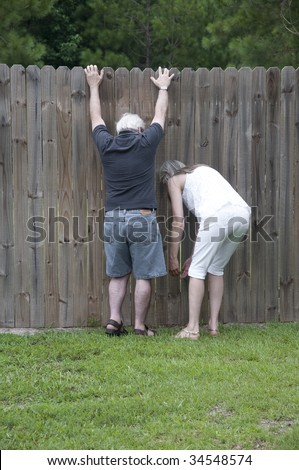 Peek over the fence to see what the neighbors are up to! - stock photo