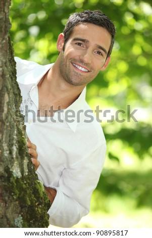 Peekaboo. Man in a white shirt peering round a tree. - stock photo