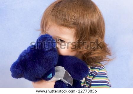 peekaboo - shy kid holding blue Teddy bear and peeking from behind blue stuffed animal toy (blue background) - stock photo