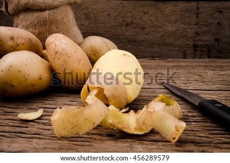 Peel fresh potatoes on rustic wooden background. Raw organic potatoes on old wooden background. - stock photo
