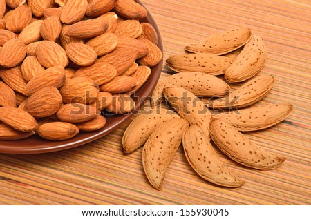 Peeled almonds on the ceramic saucer and in the nutshell on the wooden background