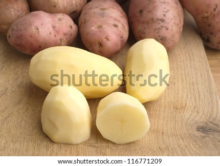 Peeled and unpeeled re potatoes on brown wooden kitchen board closeup