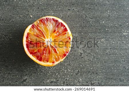 peeled blood orange on dark wood table - stock photo