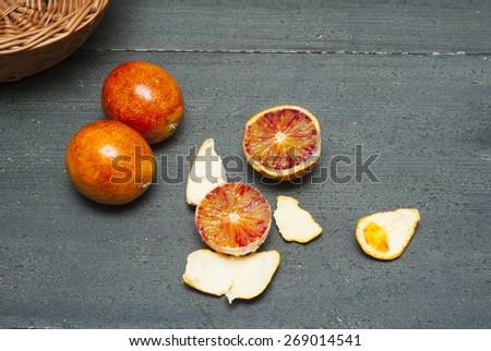peeled blood oranges on dark wood table - stock photo