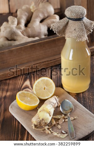 Peeled ginger root with lemons and a bottle of ginger syrup in background. Shallow dof