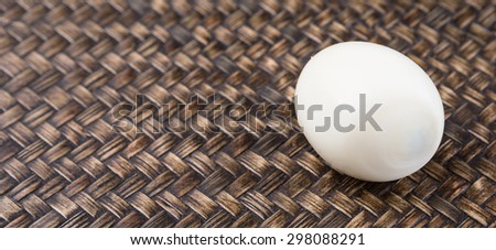 Peeled hard boiled egg over wicker background