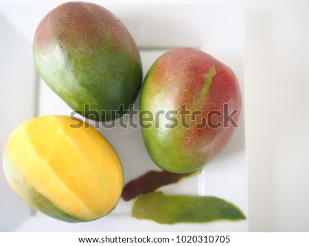 Peeled mangos, beautiful yellow red green mangos on a white plate with white background (selective focus)