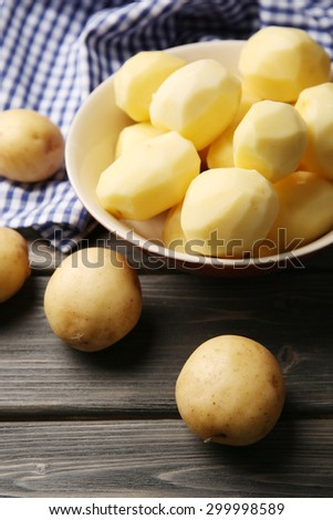 Peeled new potatoes in bowl on wooden table with napkin, closeup - stock photo