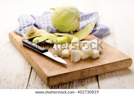 peeled organic kohlrabi and kitchen knife on a wooden board - stock photo