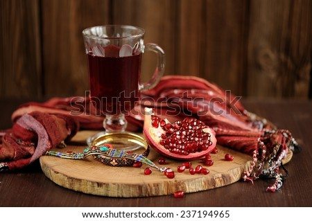 Peeled pomegranate, glass of pomegranate juice and jewerly on wooden board - stock photo