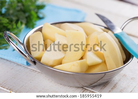 Peeled potatoes in bowl on white wooden table. Selective focus. - stock photo