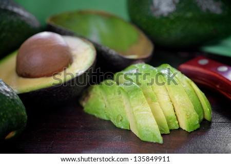 Peeled ripe avocado on the chopping board - stock photo