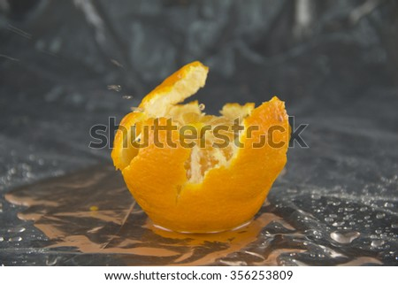 peeled tangerine and drop on a black background