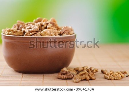 peeled walnuts in bowl of deep brown with green background, plus few scattered on bamboo table cloth - stock photo