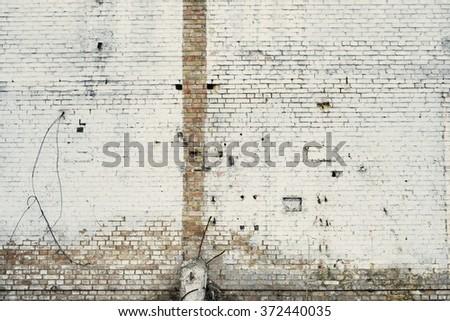 Peeled worn brick wall. Abandoned industrial facility  - stock photo