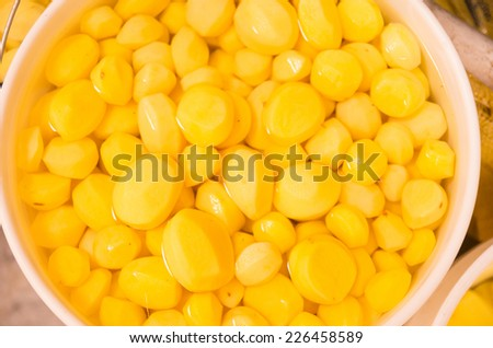 peeled yellow potatoes in a bucket market - stock photo