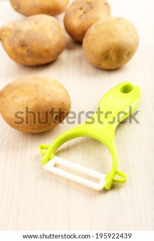 Peeler and potatoes on wooden table