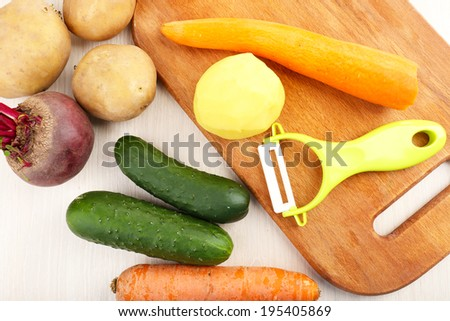 Peeler and raw vegetables on wooden table - stock photo